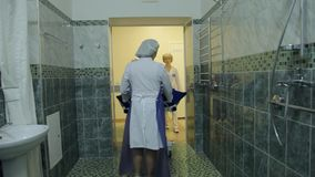 Three female nurses deliver a sedentary patient to a specialized room in order to wash it. Two female nurses deliver a sedentary patient on stretchers to a stock video footage