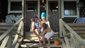 Three female sauna lovers enjoying fresh air on the porch of a traditional Finnish sauna. Three female sauna lovers happy together. Young woman, her mature mom