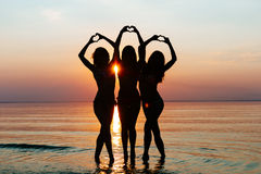 Three female silhouettes hands making a heart shape with sunset Stock Photography