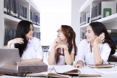 Three female students discussing in the library. Portrait of three female students doing homework together while discussing in the library Royalty Free Stock Photography