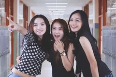 Three female students are pointing at something. Three pretty female students looking and pointing at something while standing in the school corridor Stock Photo