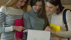 Three female students watching illustrated journal. Three attractive female studets watching illustrated journal at the college. Pretty redhead girl pointing her Royalty Free Stock Images