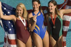 Three female swimmers celebrating victory. Holding American flag Royalty Free Stock Image