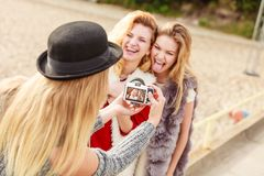 Fun woman taking pictures of females. Three females friends having fun during outdoor photo session. Woman taking pictures of two during warm autumn weather royalty free stock images