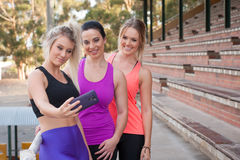 Three females taking a selfie with a mobile phone Stock Photos