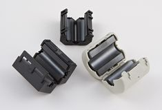 Three ferrite chokes. Three clip on ferrite choke to eliminate interference to or from radio / television / computer (white on black background Stock Images