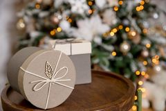 Two Festive Boxes Beige Paper Decorated White Snowflakes Linen Cord on wooden Table.Greeting Card.Christmas gifts in a. Three Festive Boxes Beige Paper Decorated royalty free stock photo