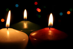 Three Festive Candles. Three Christmas candles up close, with festive lights in the background Royalty Free Stock Photos