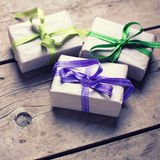 Three festive gift boxes with presents on aged  wooden backgroun Royalty Free Stock Image
