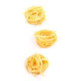 Three fettuccini pasta nests isolated on white. Royalty Free Stock Image