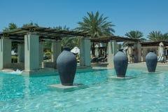 Three fictile ewers standing in line at swimming pool in arabic luxury desert resort Royalty Free Stock Photos