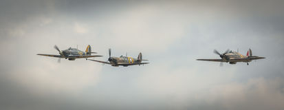 Three fighters. Biggleswade, UK - 7th May 2017: 3 vintage British Sptitfire and Hurricane fighter planes in flight Royalty Free Stock Images