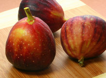 Three figs. On cutting board.  Backlit royalty free stock photos