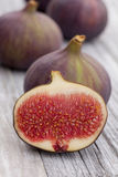 Three figs and a half. Lying on a rustic table royalty free stock photography