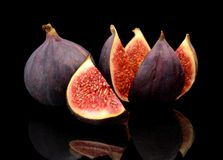 Three figs split like flower  on black background Stock Photos