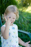 Three fingers. A vertical picture of a little blond haired and blue eyed three year old girl holding up three fingers with her eye looking between them Royalty Free Stock Photography