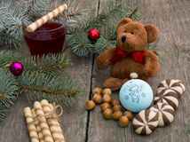 Three fir-tree branches, cup of tea, sweets and toy bear Royalty Free Stock Image
