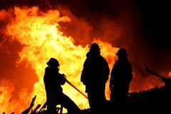 Three fire fighters and flames. Three firemen fighting a raging fire with huge flames of burning scrap timber Stock Photos