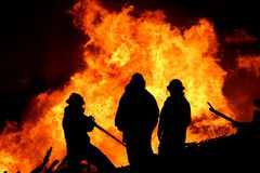 Three fire fighters and flames. Three firemen fighting a raging fire with huge flames of burning scrap timber Royalty Free Stock Photography