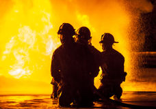 Three firefighters kneeling in front of fire Royalty Free Stock Image