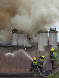 Three firefighters at work on extinguishing the real fire. Fire fighting in reality on the roof of eight floor building, which lasted up to eight hours with six Stock Photos