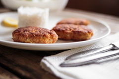 Three fish cutlet on white plate with rice Royalty Free Stock Image