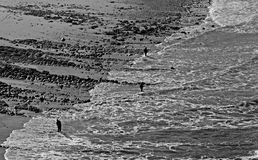 Three fisherman. Aerial rocky shoreline view of a beach with three fisherman Royalty Free Stock Images