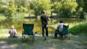 Three fisherman on the river Bank. Three fishermen sit on chairs on a river and communicate stock video footage
