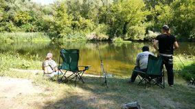 Three fisherman on the river Bank. Three fishermen sit on chairs on a river and communicate stock video