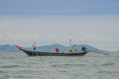 Three Fishermen on boat draw up a net to catch fish on the beach in morning . Royalty Free Stock Photos