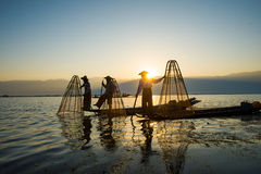 Three fishermen catches fish for food in sunrise in Inle lake Royalty Free Stock Photo