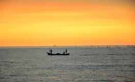 Three fishermen on a small fishing boat royalty free stock photos