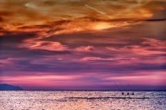 Three fishermen at sunset Stock Photos