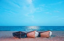 Three fishing boats on the beach. Three fishing boats moored along the beach in Dorset, United Kingdom royalty free stock image