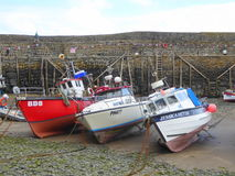 Three fishing boats in harbour. Three fishing boats aground in the small fishing harbour of Clovelly on the north Devon coast in England Royalty Free Stock Photography