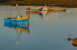 Three fishing boats at sunset. Stock Photos