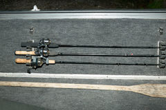 Three fishing rods neatly stowed in a holder. Three fishing rods and reels neatly stowed in a holder with an oar on the floor or deck of a dinghy ready for Royalty Free Stock Photos