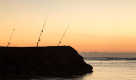 Three fishing rods at sunset over ocean Stock Images