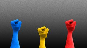 Three fists in the air with romanian flag colors royalty free stock photos