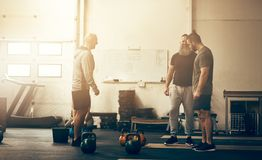 Fit men talking together while working out at a gym. Three fit men in sportswear smiling and talking together around weights between workouts in a gym stock photos