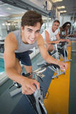 Three fit people working out on exercise bikes Royalty Free Stock Photos
