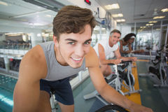 Three fit people working out on exercise bikes Royalty Free Stock Photo