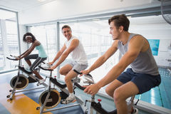 Three fit people working out on exercise bikes Royalty Free Stock Photography