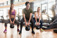 Three fit young people exercising kettlebell swings during full- stock images