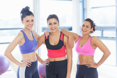 Three fit young women smiling in exercise room Royalty Free Stock Photo