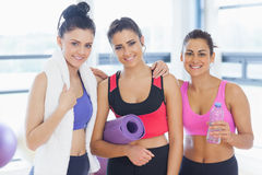 Three fit young women smiling in exercise room Royalty Free Stock Images