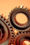 Three Fitted Gears. Closeup of three fitted gears, isolated on a peach colored background Royalty Free Stock Photos