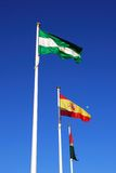 Three flagpoles, Andalusia, Spain. Three colourful flagpoles against a blue sky, Malaga Province, Andalusia, Spain, Western Europe Royalty Free Stock Images