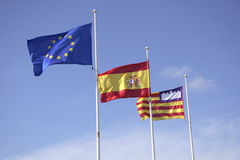 Three Flags. The flag of Europe, the flag of Spain, and the flag of the Balearic Islands, flapping in breeze against blue sky Royalty Free Stock Image