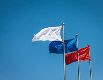 Three flags against blue sky. Royalty Free Stock Image
